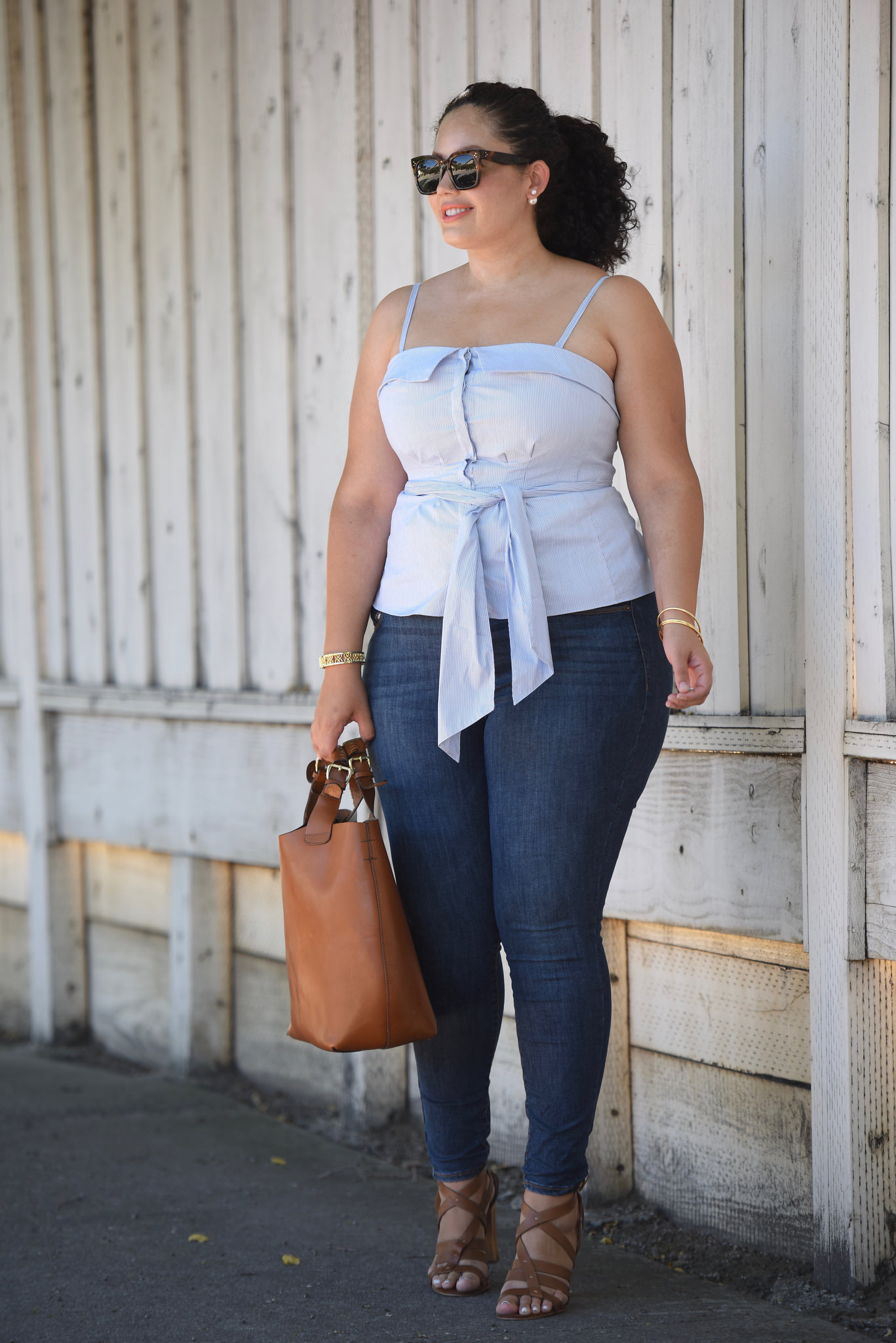 Tanesha Awasthi (girl with curves) wearing a Front Tie Bustie Topr, Skinny Jeans, cognac Tote Bag, strappy sandals