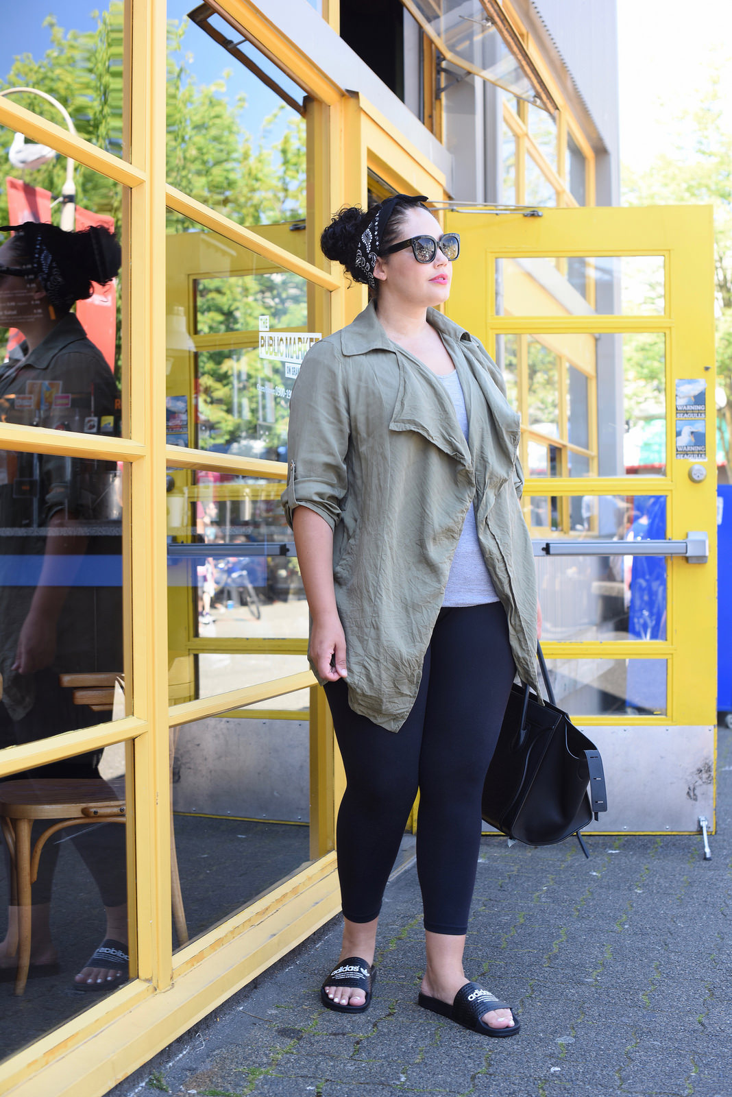 Tanesha Awasthi (formerly Girl with Curves) wearing a grey tee, waterfall utility jacket, leggings and Celine Phantom bag at the Granville Island Public Market in Vancouver.