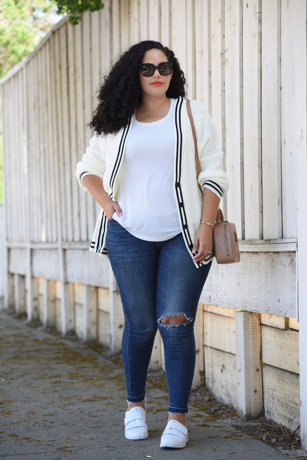 Tanesha Awasthi, also known as Girl With Curves, wearing a white tee, plus size skinny jeans, white sneakers and Chanel bag.
