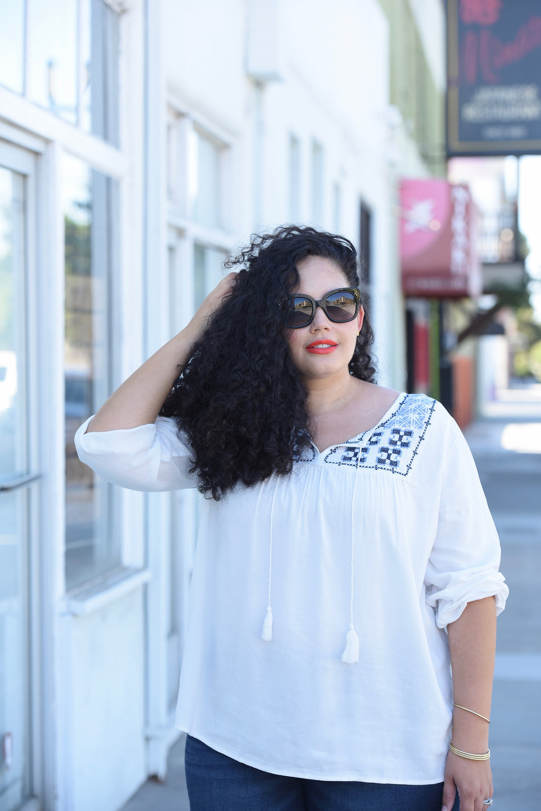 Tanesha Awasthi, also known as Girl With Curves, wearing dark wash plus size skinny jeans, a swing blouse, Celine sunglasses.